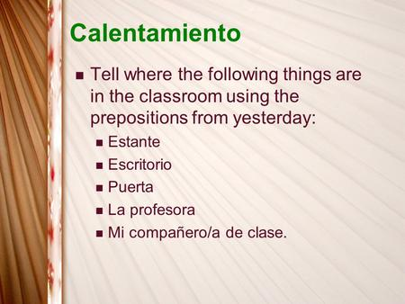 Calentamiento Tell where the following things are in the classroom using the prepositions from yesterday: Estante Escritorio Puerta La profesora Mi compañero/a.