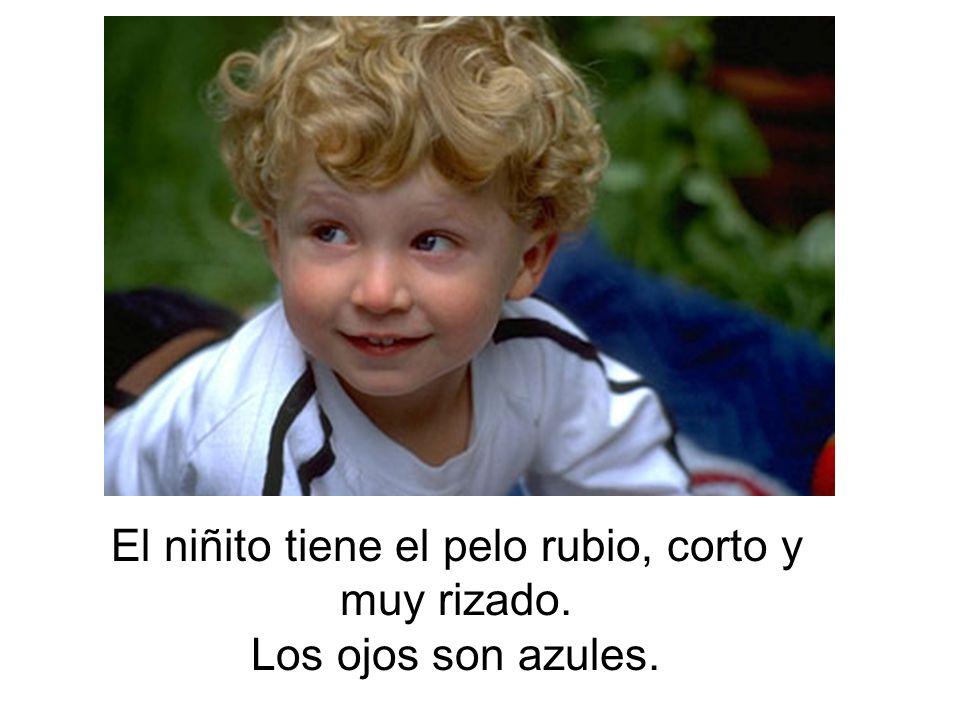 El niñito tiene el pelo rubio, corto y muy rizado. Los ojos son azules.