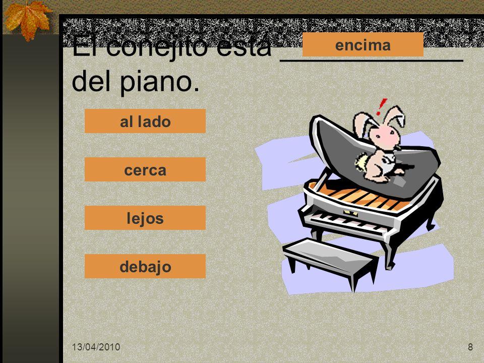 El conejito está ___________ del piano.
