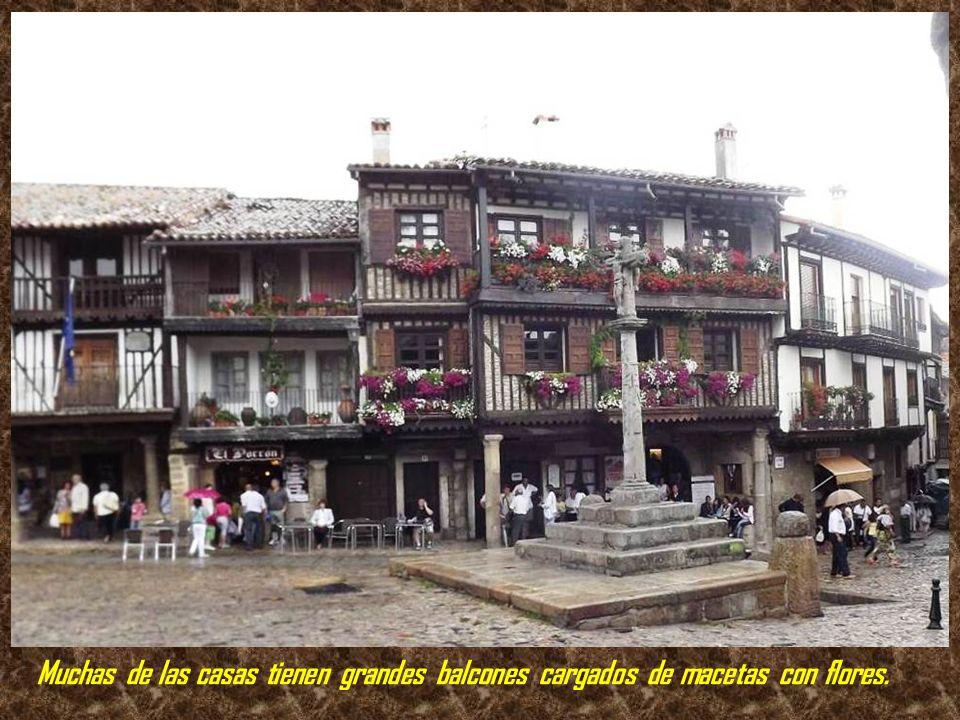 Muchas de las casas tienen grandes balcones cargados de macetas con flores.