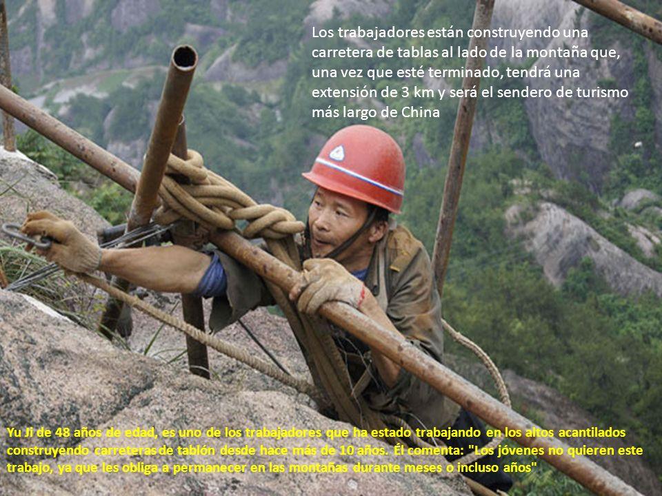Los trabajadores están construyendo una carretera de tablas al lado de la montaña que, una vez que esté terminado, tendrá una extensión de 3 km y será el sendero de turismo más largo de China