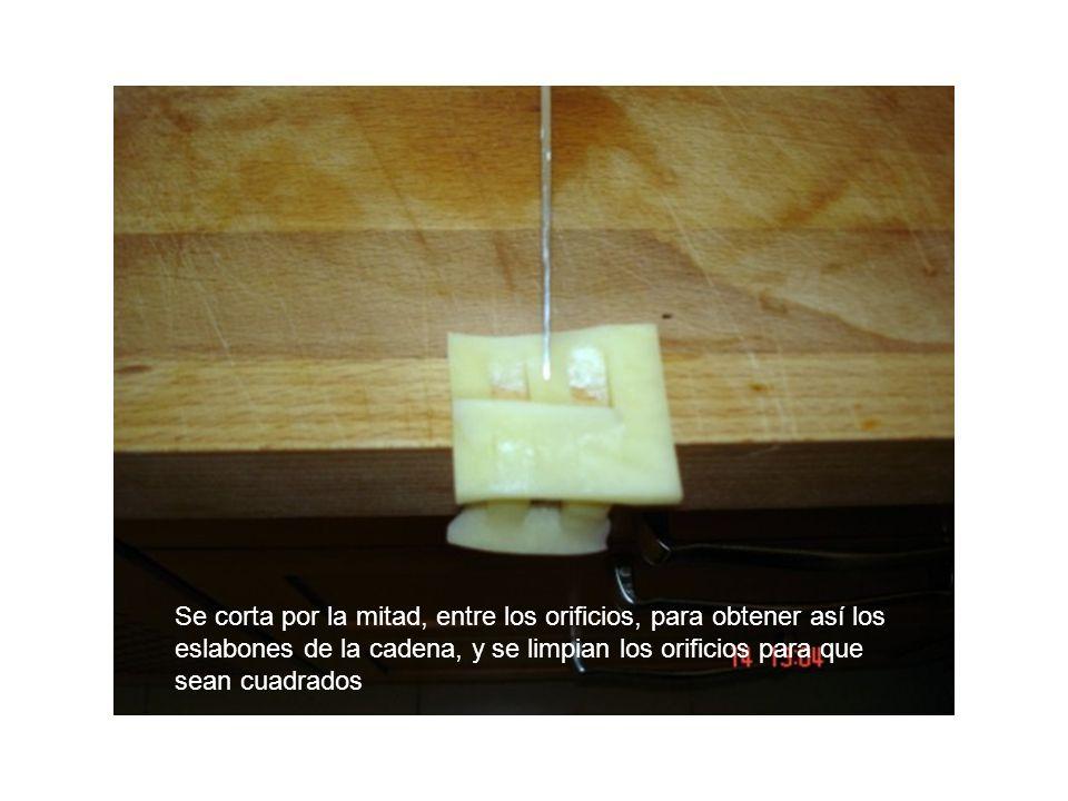 Se corta por la mitad, entre los orificios, para obtener así los eslabones de la cadena, y se limpian los orificios para que sean cuadrados