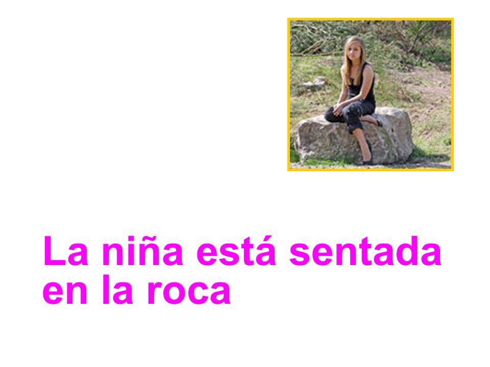 La niña está sentada en la roca