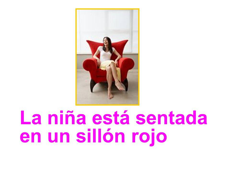 La niña está sentada en un sillón rojo