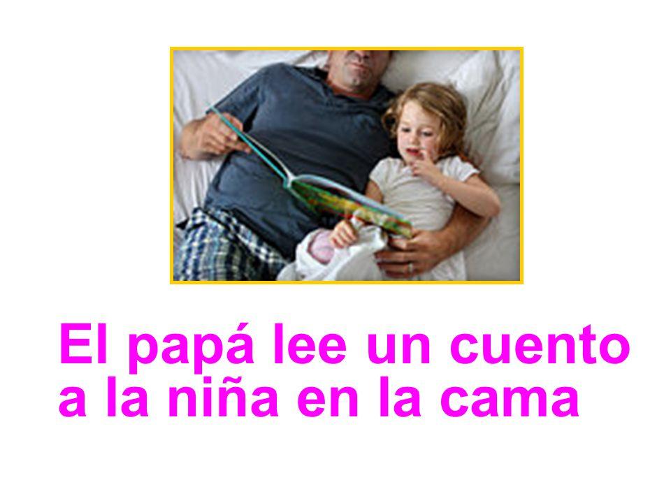 El papá lee un cuento a la niña en la cama