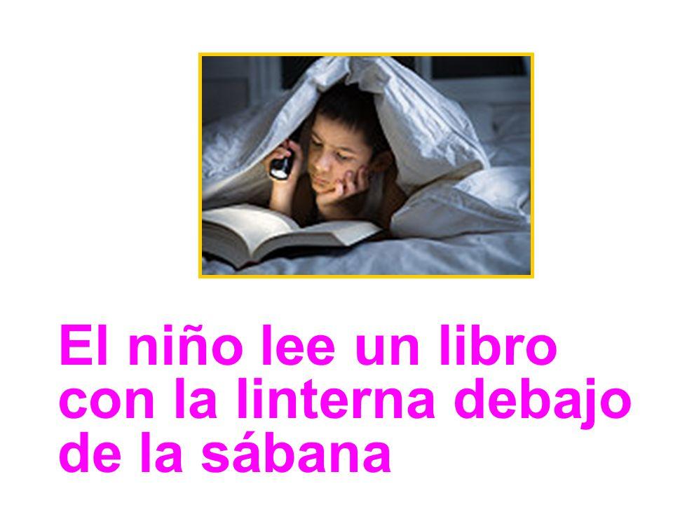 El niño lee un libro con la linterna debajo de la sábana