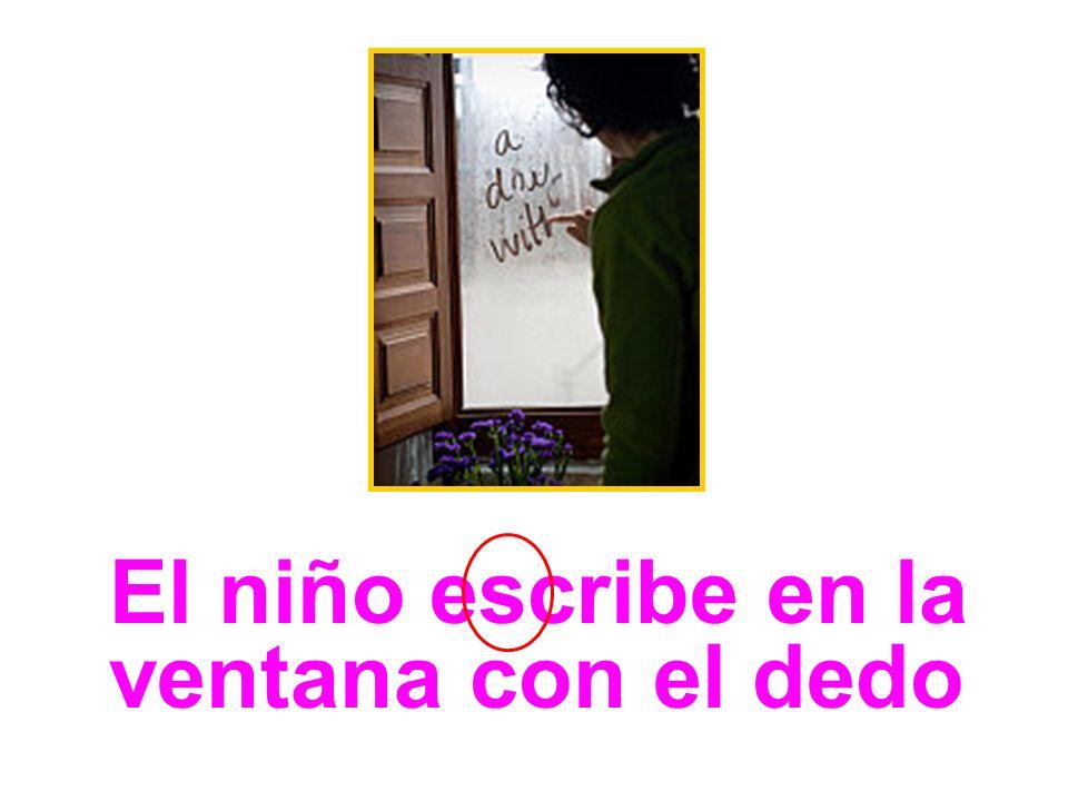 El niño escribe en la ventana con el dedo