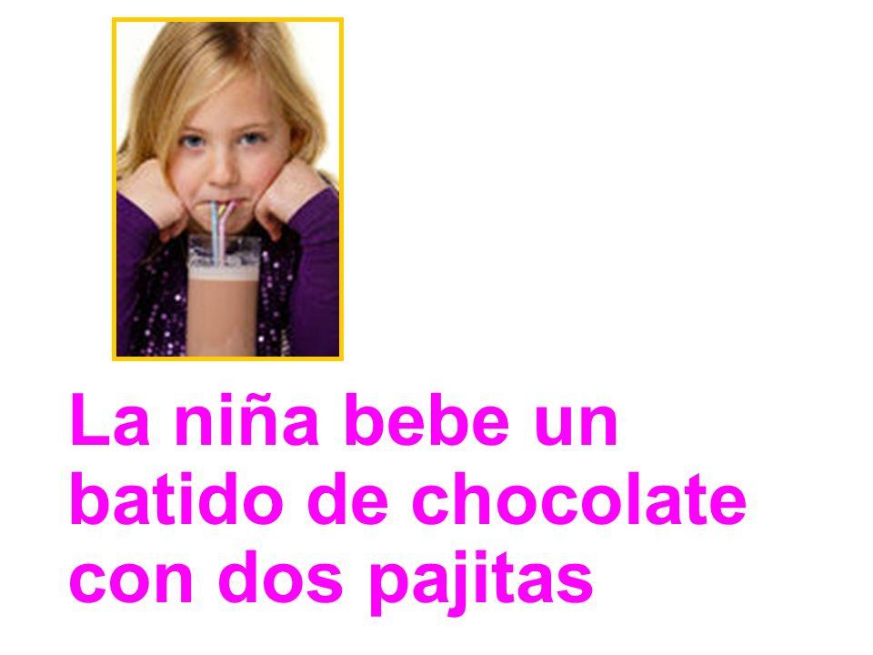 La niña bebe un batido de chocolate con dos pajitas