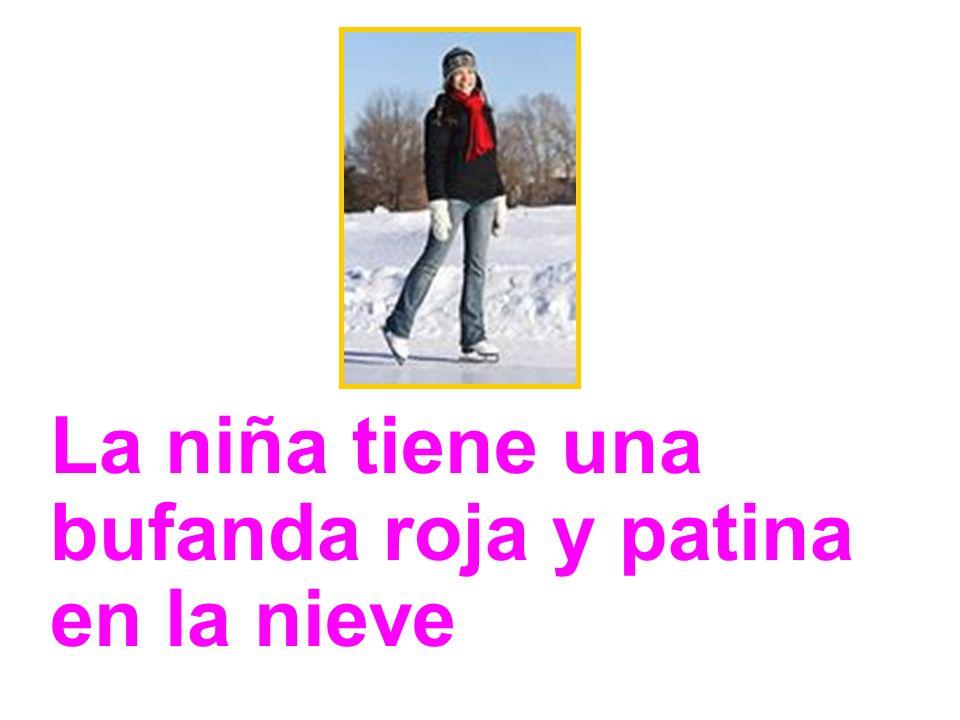 La niña tiene una bufanda roja y patina en la nieve