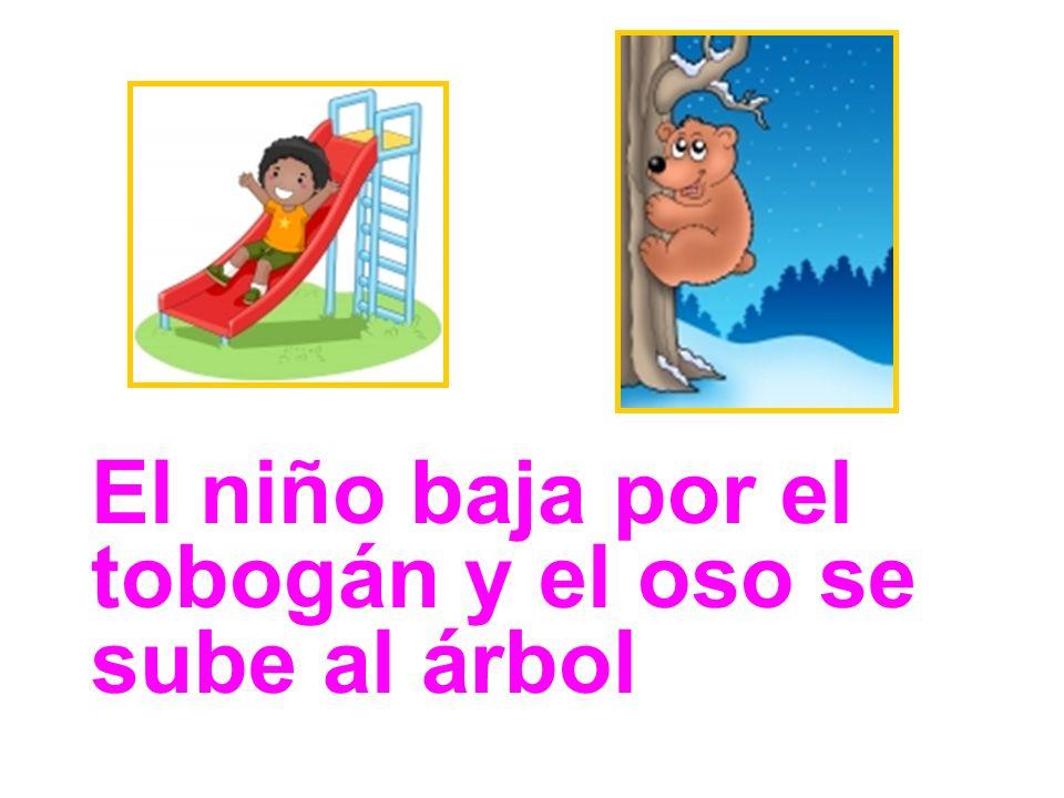 El niño baja por el tobogán y el oso se sube al árbol