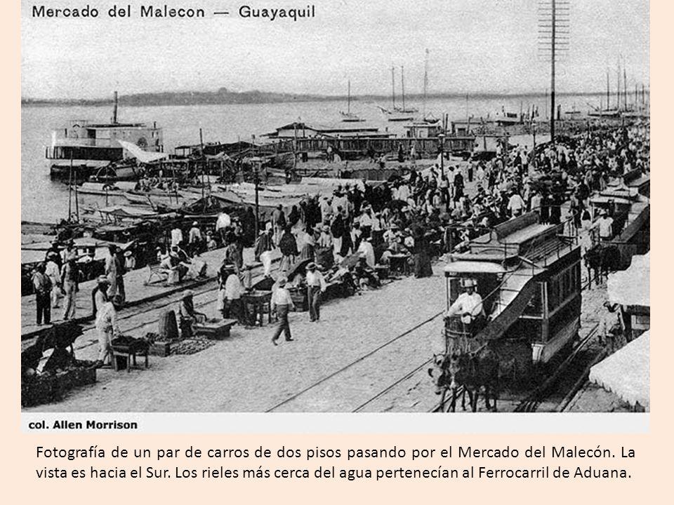 Fotografía de un par de carros de dos pisos pasando por el Mercado del Malecón.