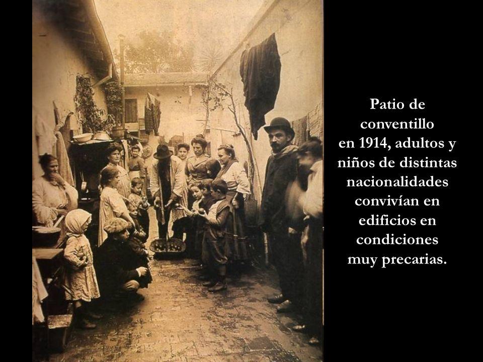 Patio de conventillo en 1914, adultos y niños de distintas nacionalidades convivían en edificios en condiciones.