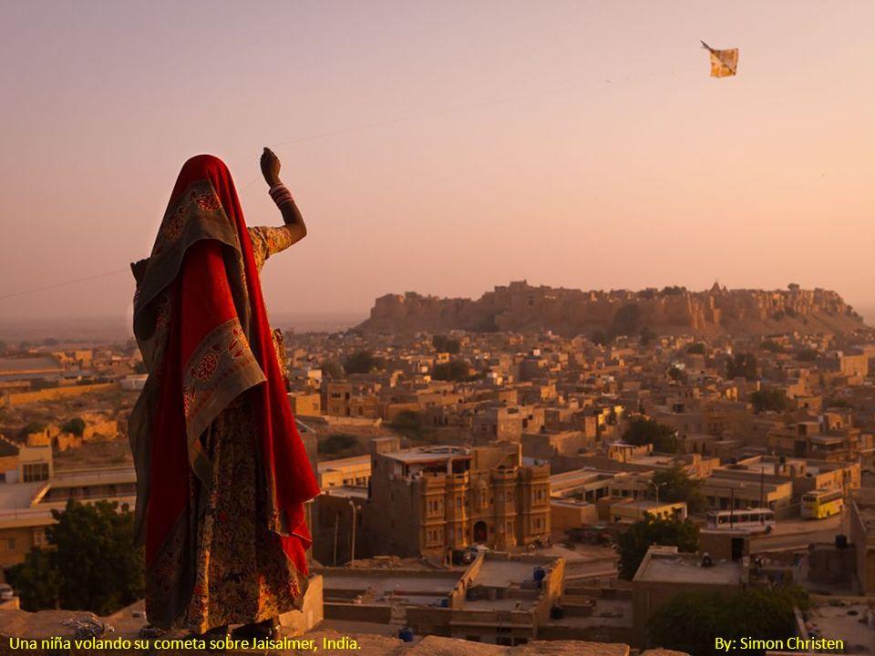 Una niña volando su cometa sobre Jaisalmer, India. By: Simon Christen