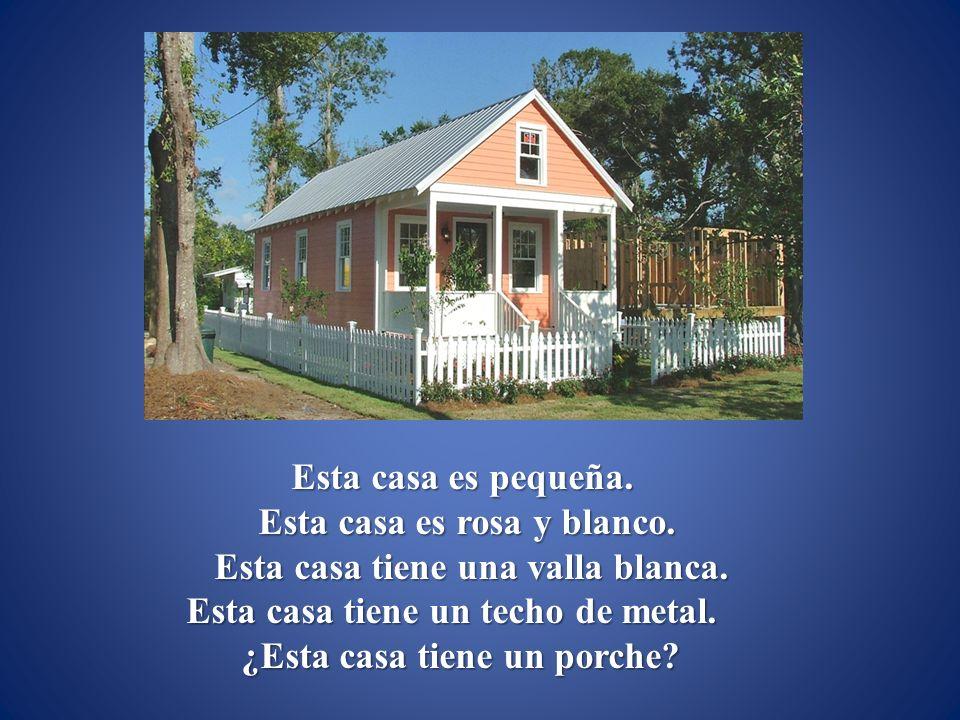 Esta casa es rosa y blanco. Esta casa tiene una valla blanca.