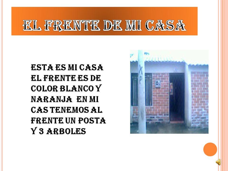 El frente de mi casa Esta es mi casa el frente es de color blanco y naranja en mi cas tenemos al frente un posta y 3 arboles.