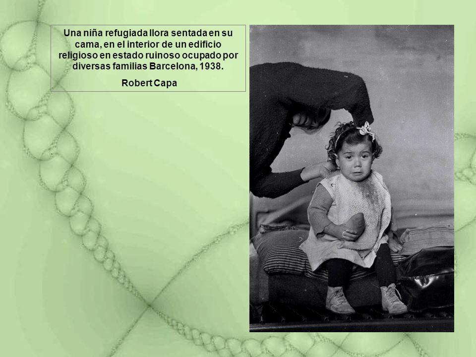 Una niña refugiada llora sentada en su cama, en el interior de un edificio religioso en estado ruinoso ocupado por diversas familias Barcelona, 1938.