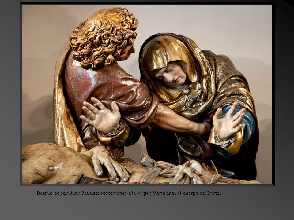 Detalle de san Juan Bautista sosteniendo a la Virgen María ante el cuerpo de Cristo.