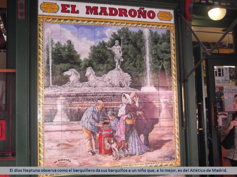 El dios Neptuno observa como el barquillero da sus barquillos a un niño que, a lo mejor, es del Atlético de Madrid.
