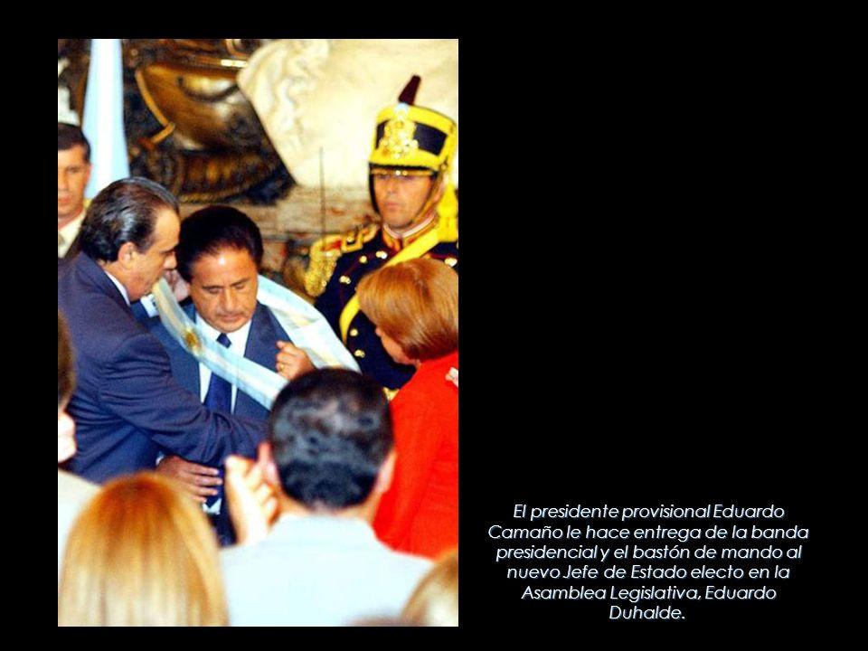 El presidente provisional Eduardo Camaño le hace entrega de la banda presidencial y el bastón de mando al nuevo Jefe de Estado electo en la Asamblea Legislativa, Eduardo Duhalde.