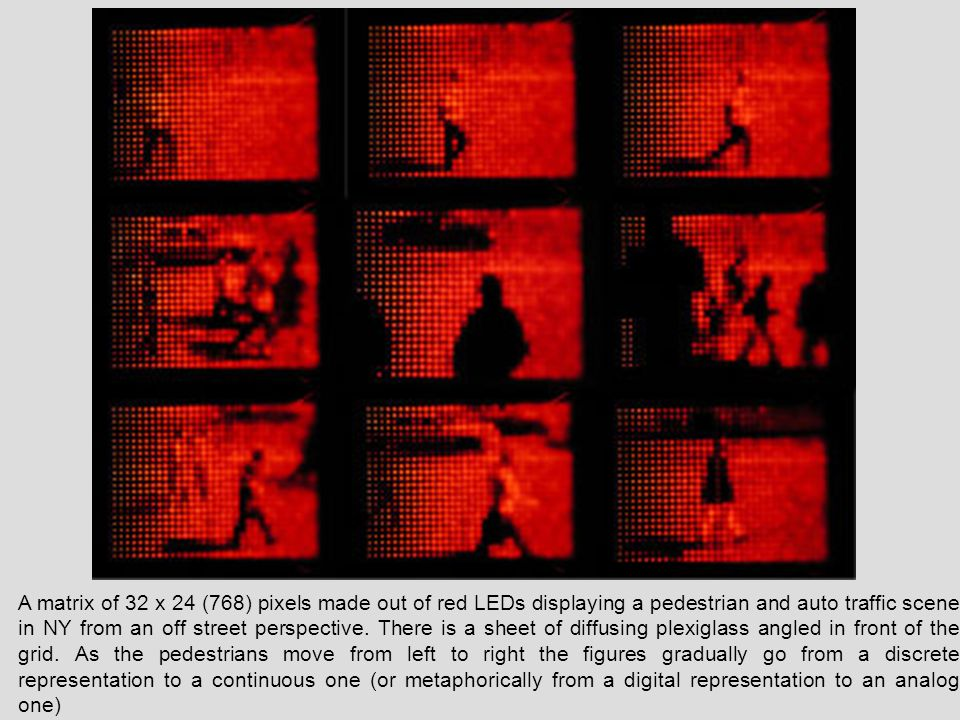 A matrix of 32 x 24 (768) pixels made out of red LEDs displaying a pedestrian and auto traffic scene in NY from an off street perspective.