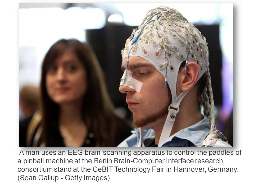 A man uses an EEG brain-scanning apparatus to control the paddles of a pinball machine at the Berlin Brain-Computer Interface research consortium stand at the CeBIT Technology Fair in Hannover, Germany.