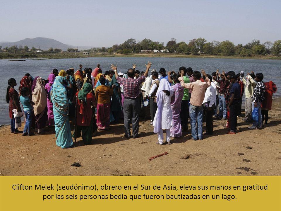 Clifton Melek (seudónimo), obrero en el Sur de Asia, eleva sus manos en gratitud por las seis personas bedia que fueron bautizadas en un lago.