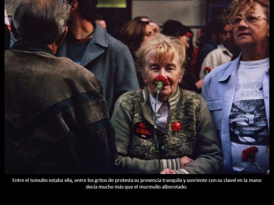 Entre el tumulto estaba ella, entre los gritos de protesta su presencia tranquila y sonriente con su clavel en la mano decía mucho más que el murmullo alborotado.