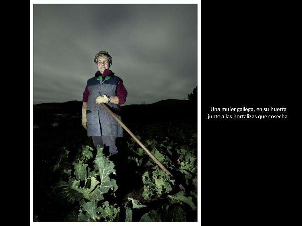 Una mujer gallega, en su huerta junto a las hortalizas que cosecha.