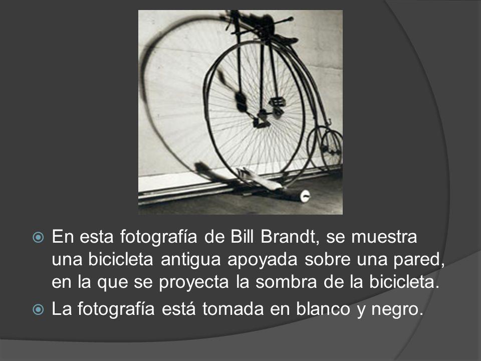 En esta fotografía de Bill Brandt, se muestra una bicicleta antigua apoyada sobre una pared, en la que se proyecta la sombra de la bicicleta.