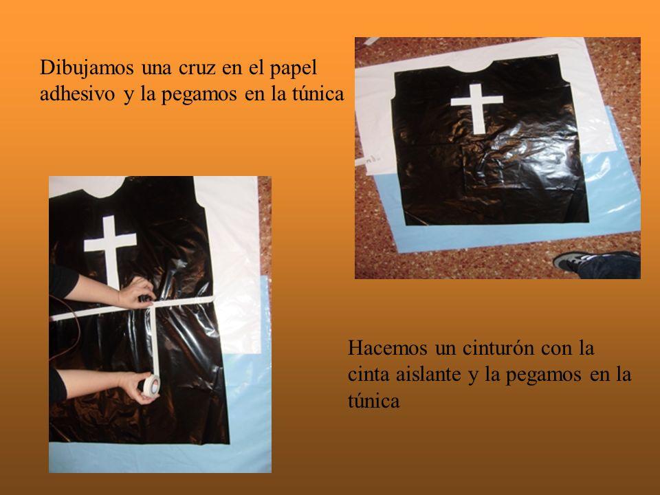 Dibujamos una cruz en el papel adhesivo y la pegamos en la túnica