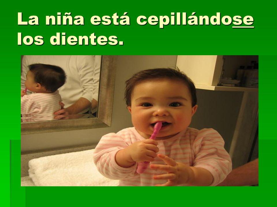 La niña está cepillándose los dientes.