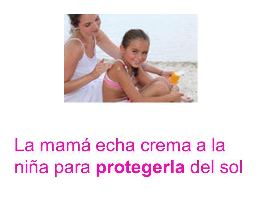 La mamá echa crema a la niña para protegerla del sol