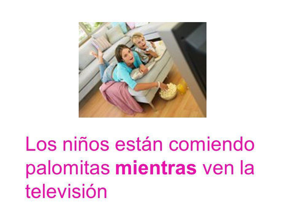 Los niños están comiendo palomitas mientras ven la televisión