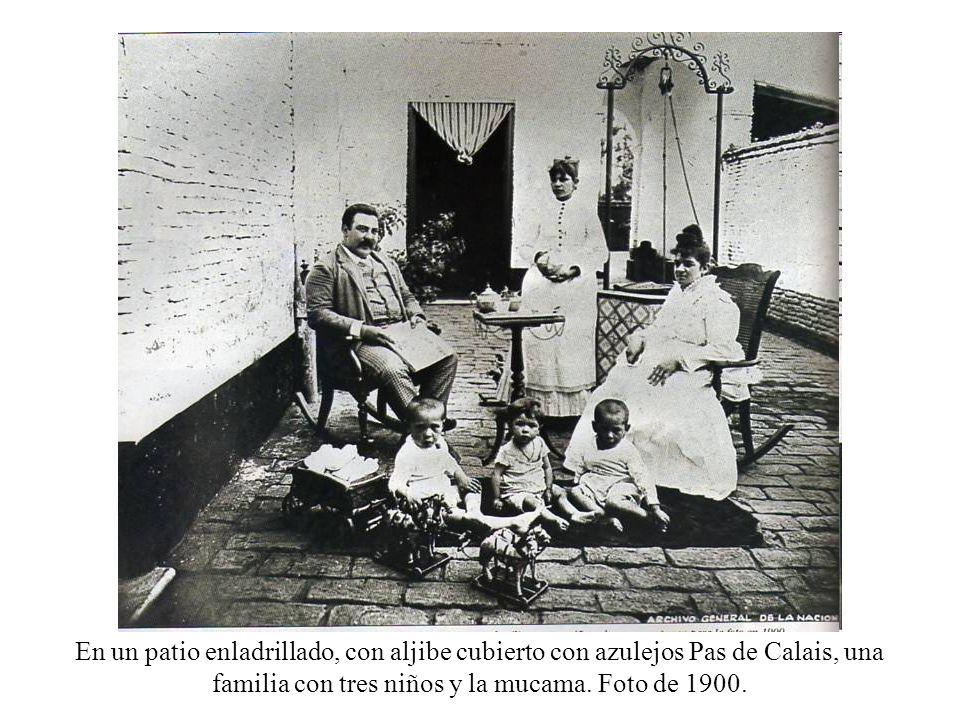 En un patio enladrillado, con aljibe cubierto con azulejos Pas de Calais, una familia con tres niños y la mucama.