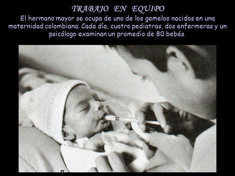 TRABAJO EN EQUIPO El hermano mayor se ocupa de uno de los gemelos nacidos en una maternidad colombiana.