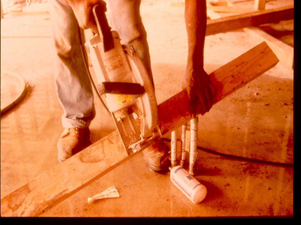 Trabajador usando sierra eléctrica y parado en agua