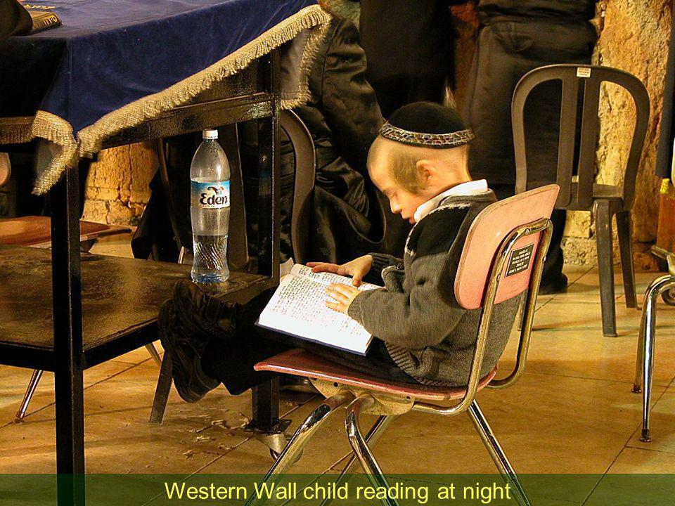 Western Wall child reading at night
