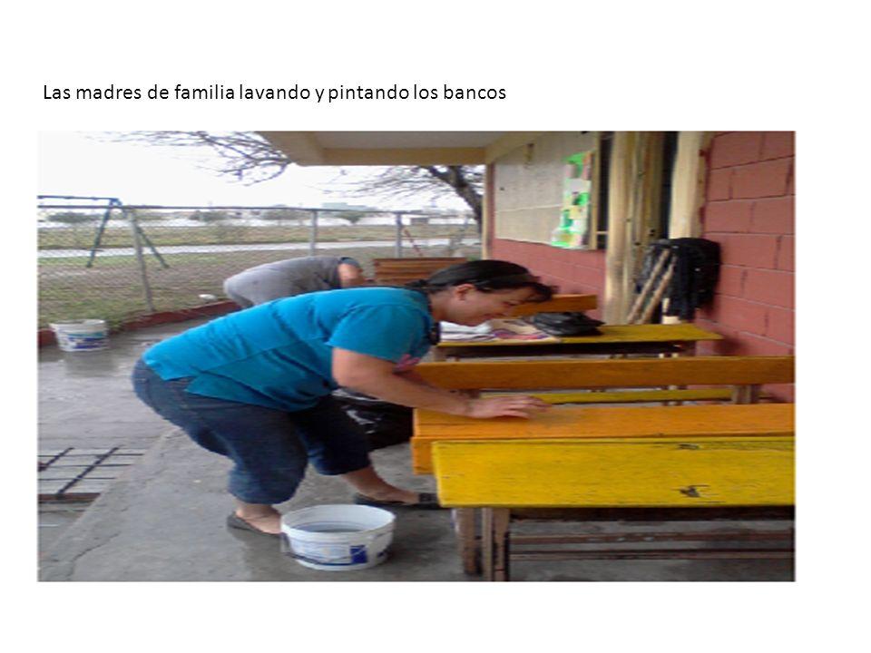 Las madres de familia lavando y pintando los bancos