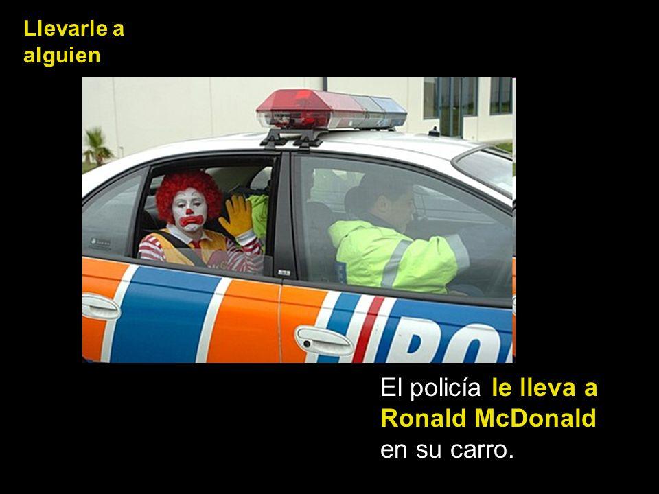 El policía le lleva a Ronald McDonald en su carro.
