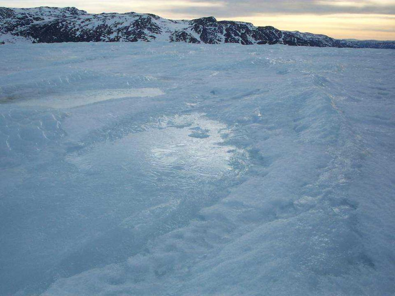 Even early in the Spring, melt lakes begin to form and partially refreeze at night. Each year, more melting occurs, it starts earlier, and it lasts longer.