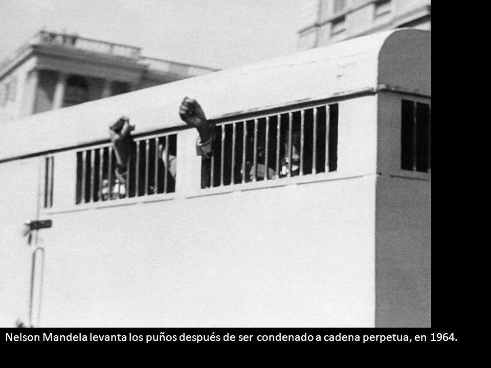 Nelson Mandela levanta los puños después de ser condenado a cadena perpetua, en 1964.