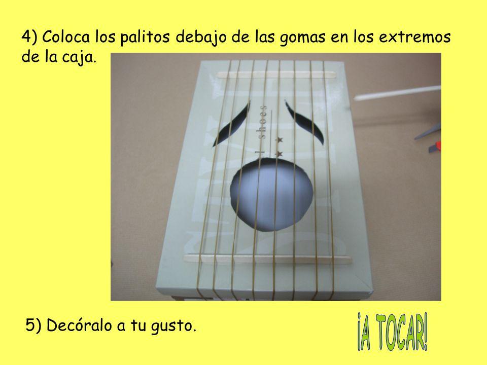 4) Coloca los palitos debajo de las gomas en los extremos de la caja.