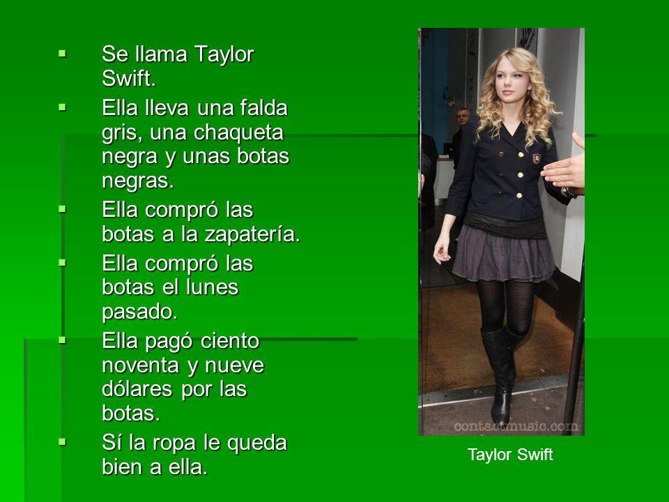 Ella lleva una falda gris, una chaqueta negra y unas botas negras.