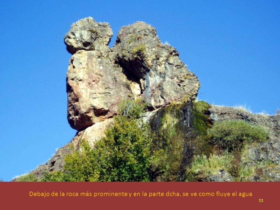 Debajo de la roca más prominente y en la parte dcha