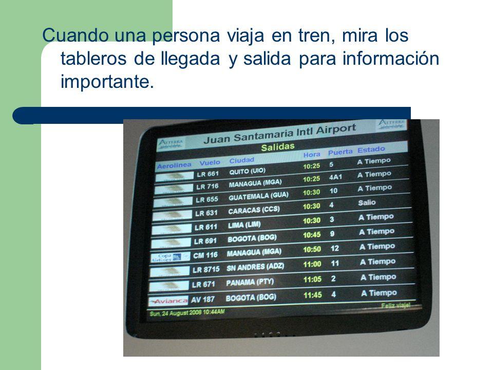 Cuando una persona viaja en tren, mira los tableros de llegada y salida para información importante.