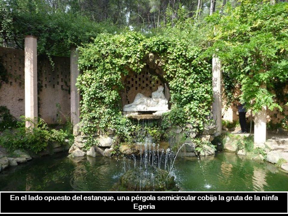 En el lado opuesto del estanque, una pérgola semicircular cobija la gruta de la ninfa Egeria