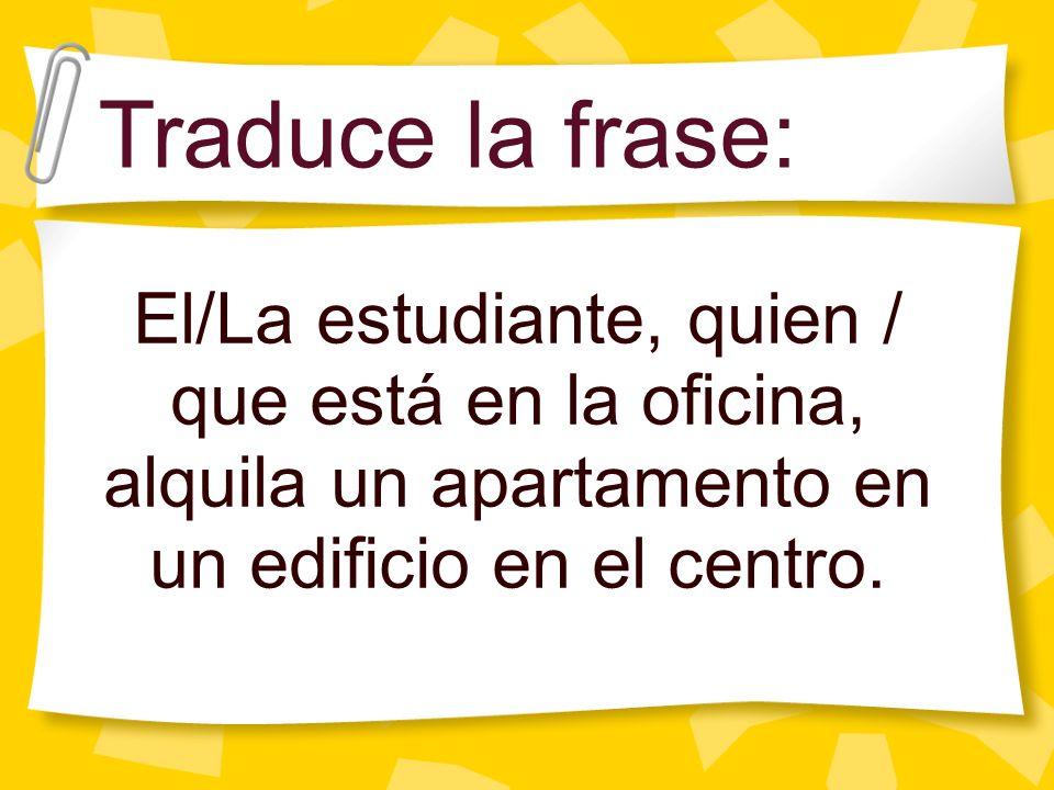 Traduce la frase: El/La estudiante, quien / que está en la oficina, alquila un apartamento en un edificio en el centro.