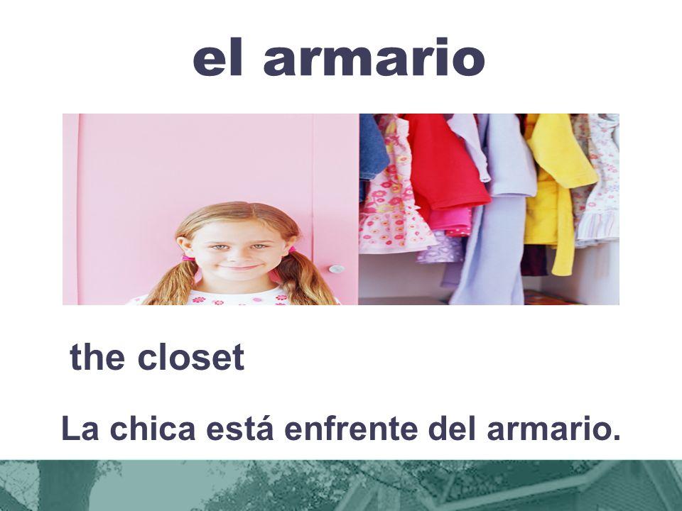 La chica está enfrente del armario.