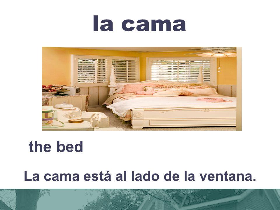 La cama está al lado de la ventana.