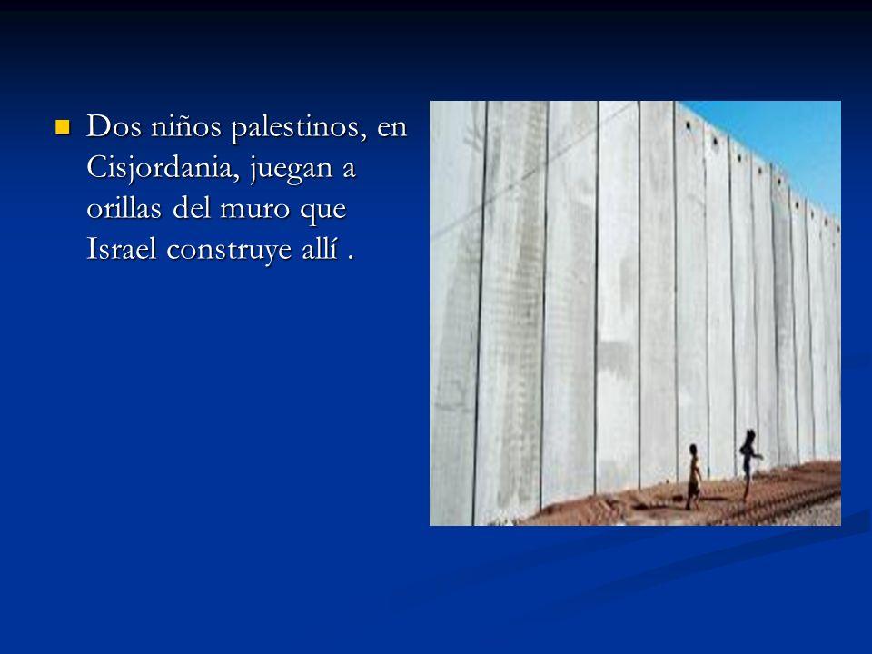 Dos niños palestinos, en Cisjordania, juegan a orillas del muro que Israel construye allí .